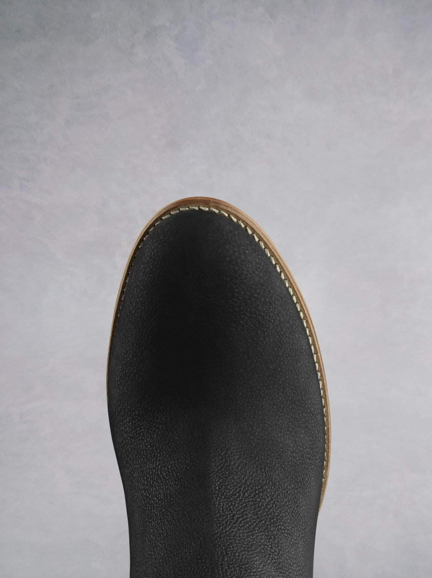 This black ankle boot has an almond toe shape highlighted by contrast white stitching.