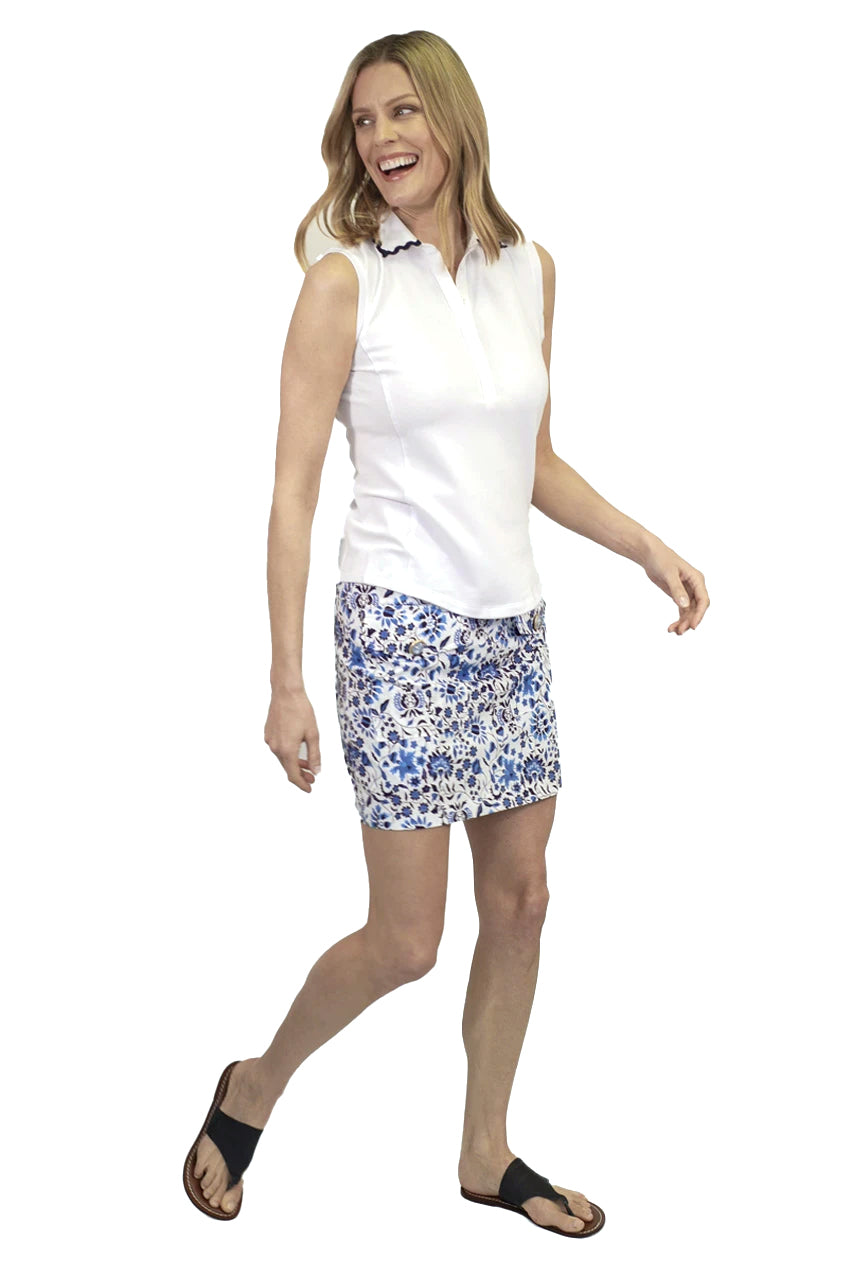 Women's white sleeveless pique cotton golf top. Fashionable ladies golf apparel. Button up sleeveless top with navy ric rac trim on collar.