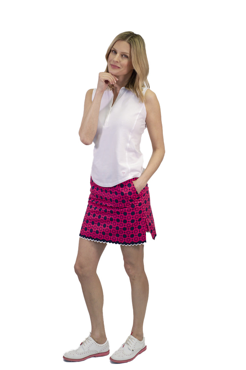 Women's hot pink and navy stretch designer golf skort with bottom trim. Women's white sleeveless golf polo
