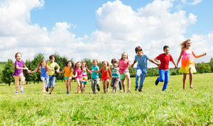 Children holding hands running through a field