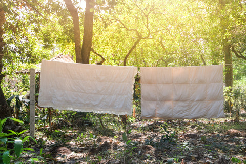 Two white blankets hanging on a clothesline drying In the afternoon Sun in Countryside, Thailand