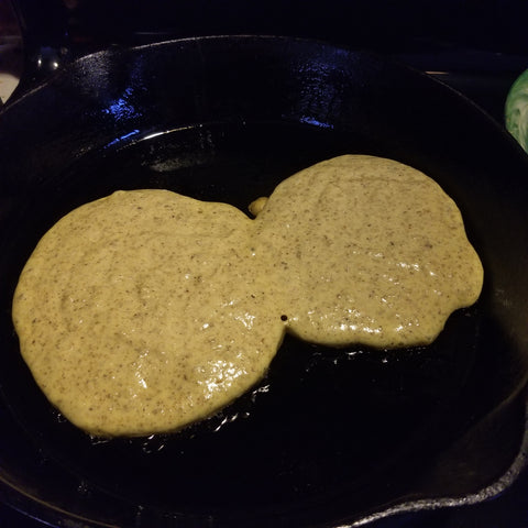 Buckwheat pancakes being cooked on a cast iron skillet