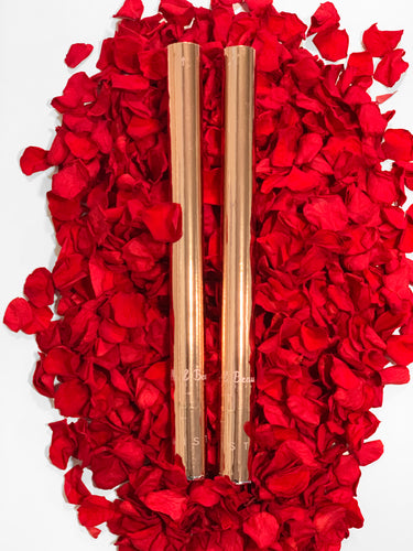 Two Rose Petal Cannons sitting on a bed of red rose petals