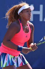 Naomi Osaka returning a serve in a pink top white cap and multicolored skirt