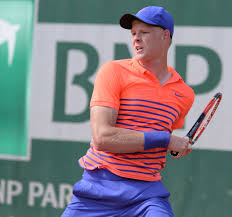 Kyle Edmund making a forehand return on clay in and orange and blue outfit