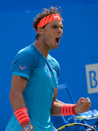 Rafa Nadal celebrating with a fist pump and wearing a turquoise blue shirt and matching orange head bandanna and wristbands