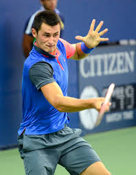 Tomic making a forehand at the back of the court