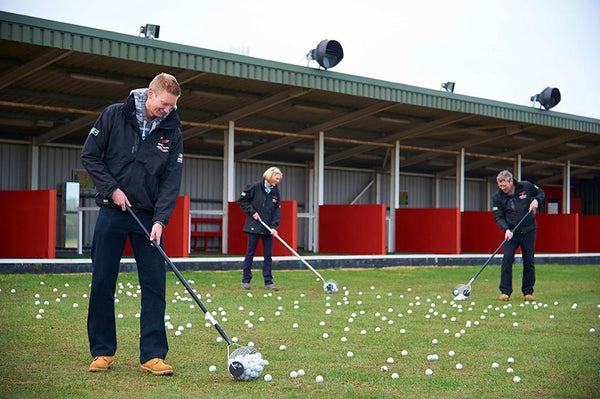 Three people using the Bagbuddy golf ball retriever to pick up golf balls on a driving range