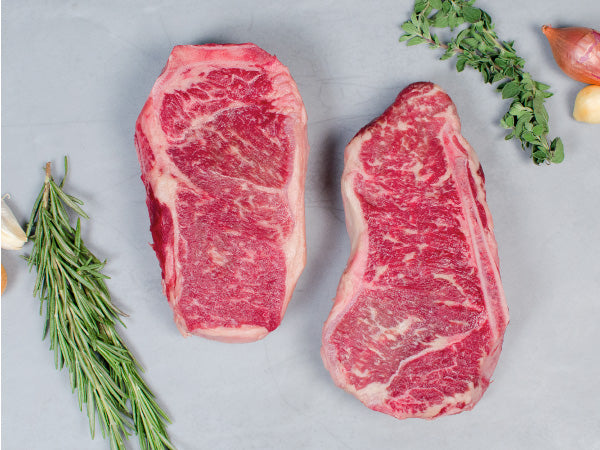 BONE-IN STRIP STEAK, OUR SIGNATURE WAGYU, Two bone-in steaks
