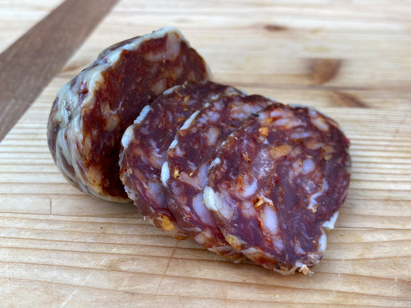 SPICY HERITAGE SALAMI — pork salami seasoned with red chiles, espelette pepper, and wrapped in caul fat by Smoking Goose, Three 5 oz packs