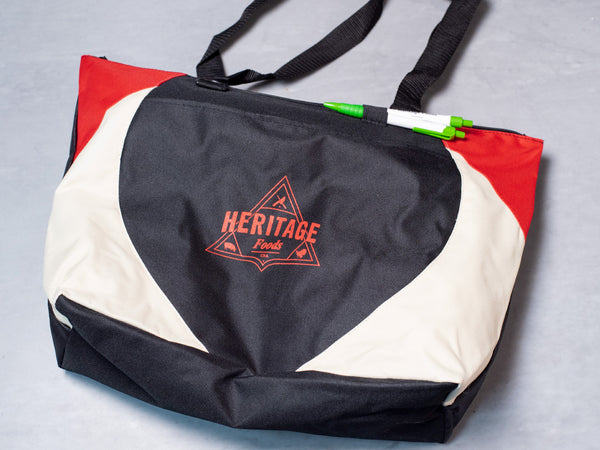NEW! HERITAGE FOODS TOTE BAG with Heritage Pen included, featuring an open front pocket, zippered closure, and two elastic pen holders on the front