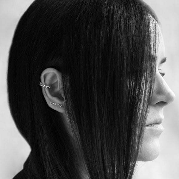 A black and white portrait of Alex Eagle in her jewellery designs created in collaboration with Otiumberg.