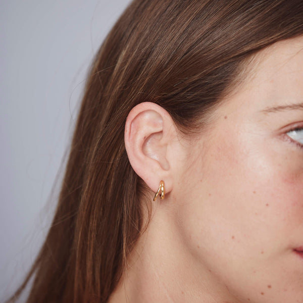A side profile of a woman is shown with the gold double hoop styled in the first piercing.