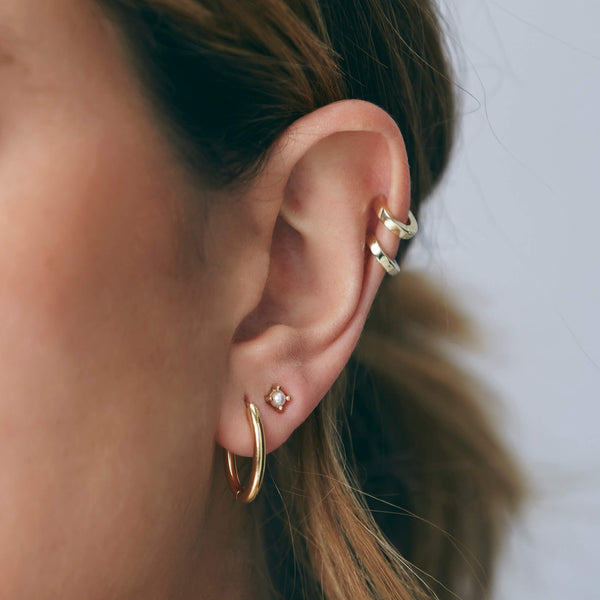 A pair of yellow gold huggie hoops are styled in the helix piercings of the ear.