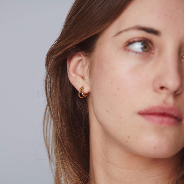 The gold duo hoops offer a stacked look with just one earring, here worn alone on a model as part of the Otiumberg Collection.
