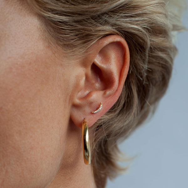 Crescent stud is worn in the upper lobe piercing with the chunky gold hoops in the first piercing. The model has short blonde hair.