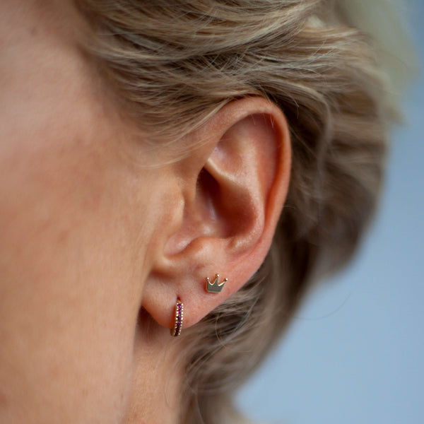 A young blonde model wears the gold crown stud in her second piercing with the black diamond huggie hoop in the first piercing