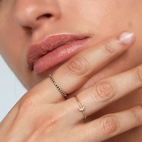 close up image of a model wearing the 9-karat solid yellow gold black diamond ring