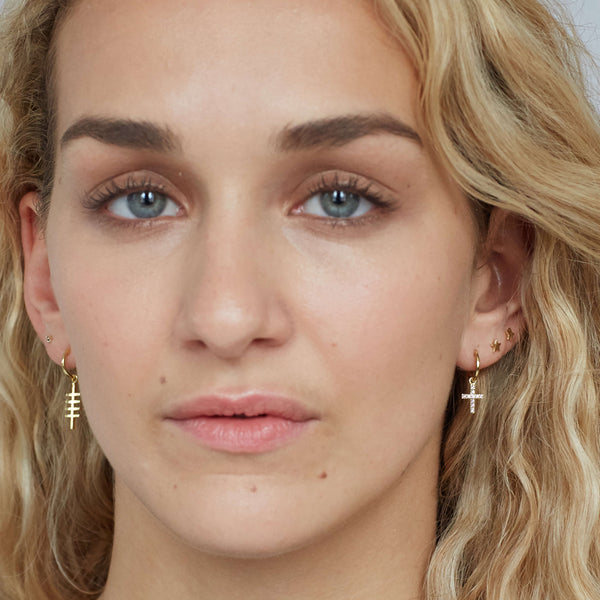 a forward facing image of a woman's face, in one ear she has a small blue topaz gold cross hoop and in the other is a small gold fishbone style earring