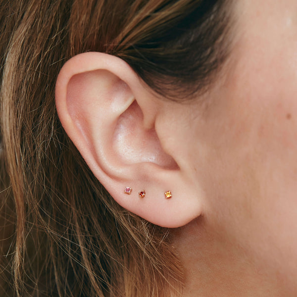 Birthstone studs sold on otiumberg are stacked up the ear lobe on a young female model