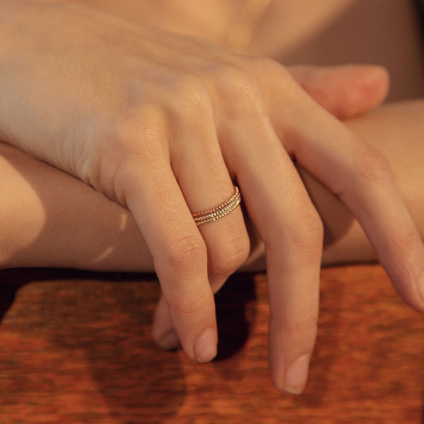 Silver, Gold and Rose Gold Delicate Twisted Rings shown on a Hand