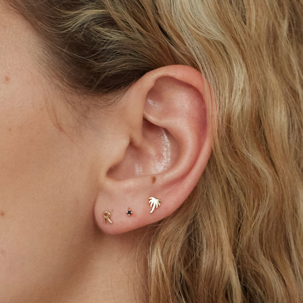 Solid Yellow Gold Palm Tree Stud, pictured here in an ear lobe stacked with an R stud and a black diamond stud.