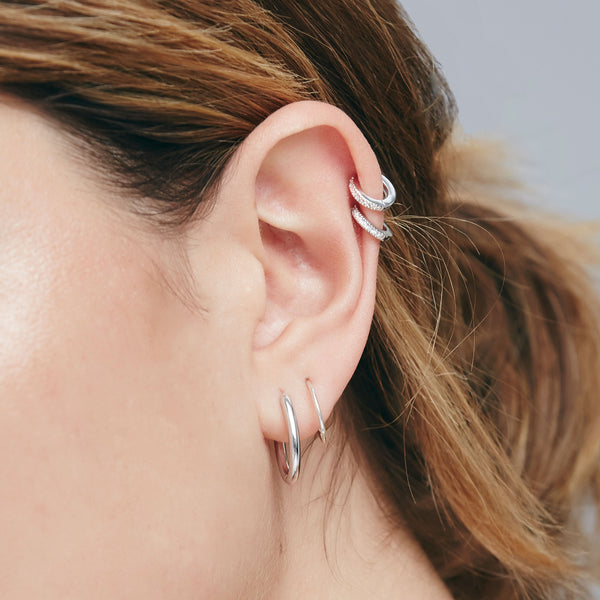 an ear wearing a silver oval hoop in the lobe