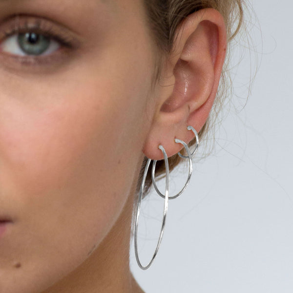 The small silver hoops with an endless closure stacked with medium and large silver hoops.