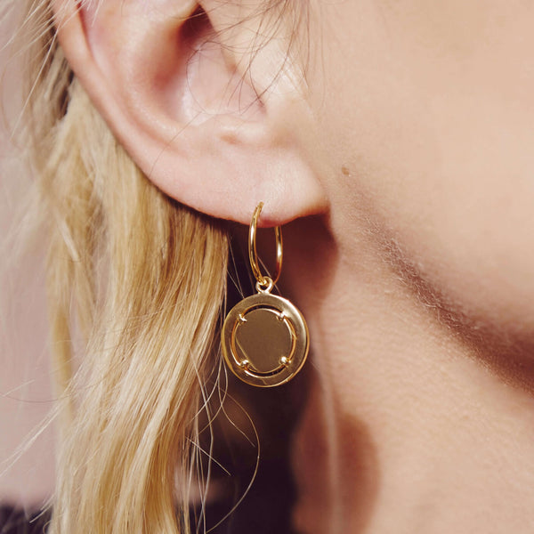 an ear with a gold hoop earring in with a gold coin pendant handing from he hoop