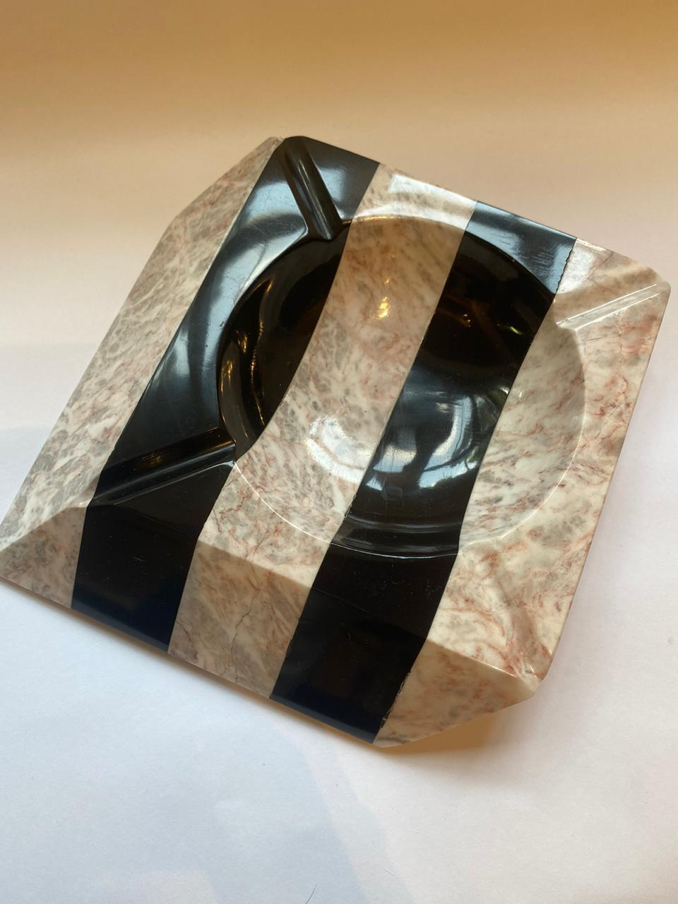 Pink marble ashtray with black.
