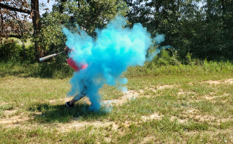 Individual hitting a blue smoke filled baseball announcing them having a baby boy