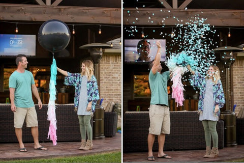 Couple popping their gender reveal balloon filled with blue confetti celebrating their baby boy