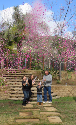 Family posing together outside covered in pink confetti to announce the parents having a baby girl.