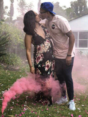 Couple posing with pink smoke to reveal the gender of their baby.
