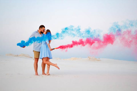 Couple posing on a beach with pink and blue smoke.