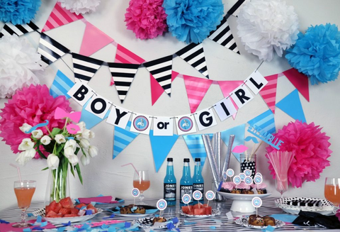 "Table decorated with blue and pink themed items for a gender reveal party. With a banner that reads ""boy or girl"" hanging up."