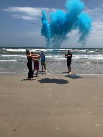 Family celebrating having a baby boy with a blue smoke cannon on the beach.