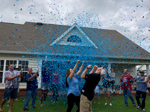 Couple celebrating the gender of their baby with family and friends, by shooting blue confetti.