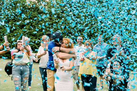 Couple surrounding by family outside, posing with blue confetti to announce having a baby boy