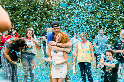 Couple hugging, surrounded by friends and family with blue confetti falling down.