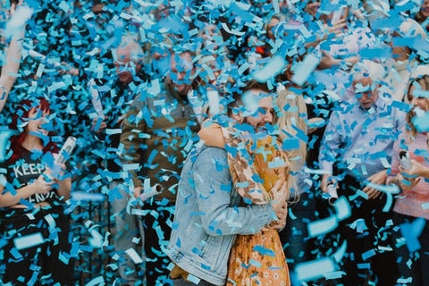 Couple hugging while being covered in blue confetti, celebrating having a baby boy.