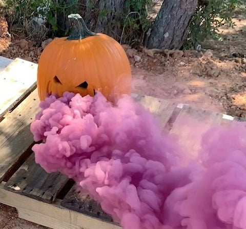 Picture of a carved pumpkin with pink smoke coming out of it.