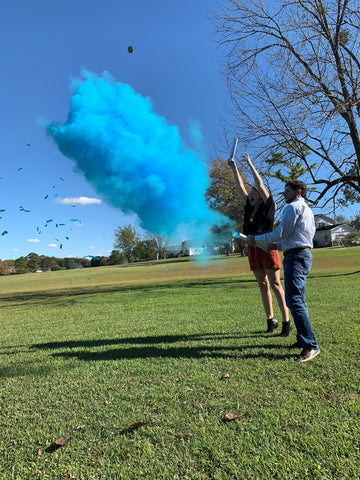 Couple posed outside with blue smoke and confetti.