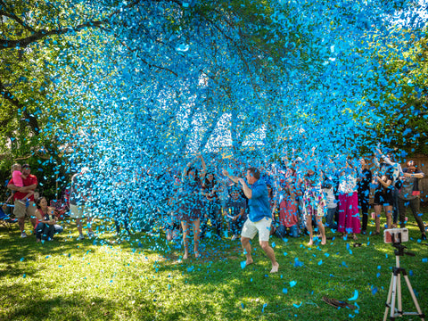 Family and friends shooting confetti cannons exposing blue confetti. Celebrating the couple having a boy.