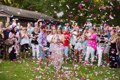 Family and friends surrounding a couple outside, while shooting pink confetti cannons.