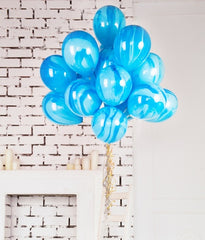 blue balloons tied to a table with a white brick wall as a background.