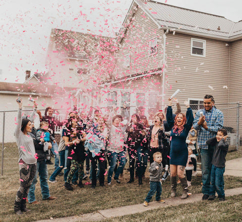 Family and friends celebrating a couple having a baby girl by shooting pink confetti everywhere.