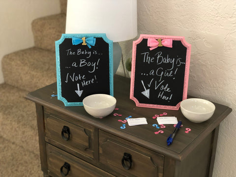 Two bowls on a table with respective signs indicating to put your name in which one you believe the sex of the baby to be.