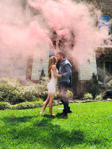 A couple posing with pink smoke bombs, announcing them having a baby girl