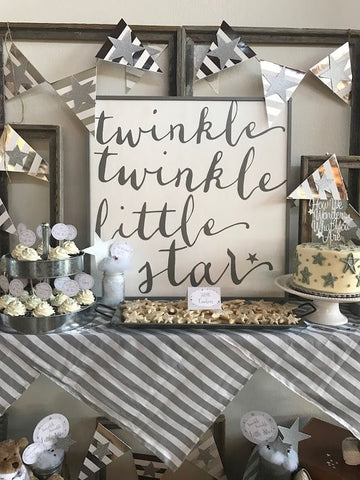"Table with grey decorations and grey colored sweets on it. With a sign that says ""twinkle twinkle little star"" on it."